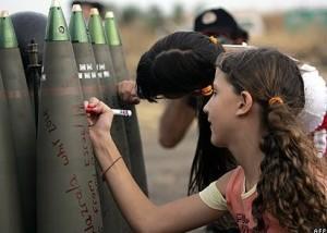 Żydowskie dziewczynki piszą życzenia na bombach, które wkrótce spadną Palestyńczykom na głowę, fot: AFP