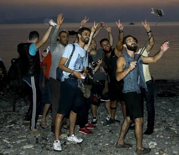 Muzułmańscy imigranci, którzy właśnie nielegalnie dotarli do Grecji robią sobie fotkę na zdobycznym terenie, fot: Reuters