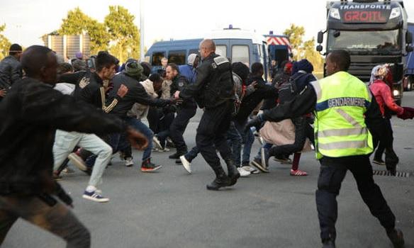 Żandarmeria w Calais próbuje zatrzymać imigrantów przed szturmem Eurotunelu, fot: Daily Express